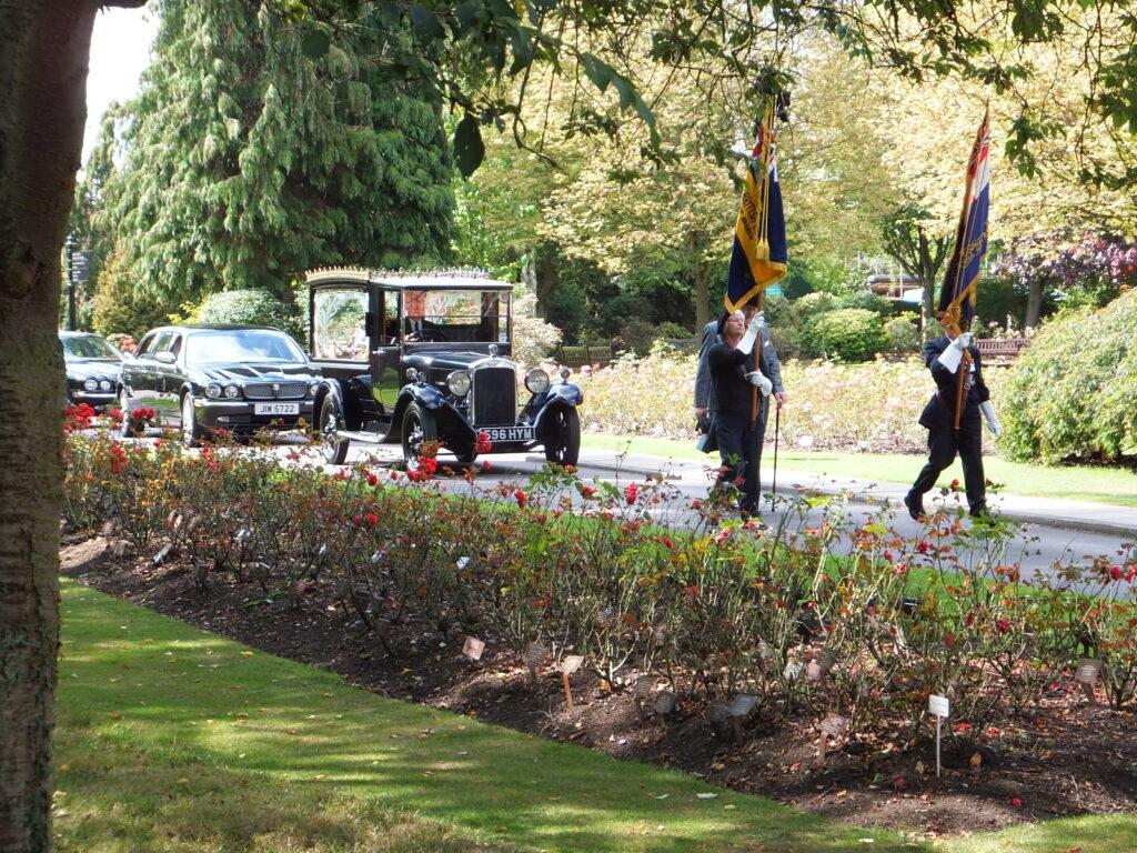 Vintage Austin Hearse escorted by British Legion Standard Bearers