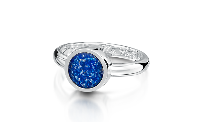 A white gold ring inset with blue glass with cremated remains incorporated